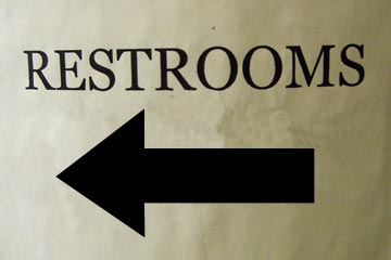 Restroom Sign With Big Black Arrow Pointing To The Left